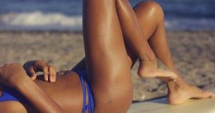 Wollüstige junge Frau, die in einem Bikini ein Sonnenbad nimmt Stockbild