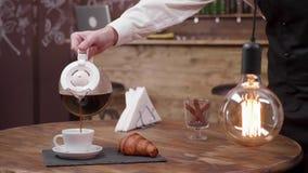 Wolno nalewać filiżankę świeża ciemna kawa w białej filiżance zbiory wideo