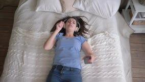 Wolny czas spada na łóżku i słucha piosenki od przyjemności muzyki, wesoło kobieta w słuchawki telefonu komórkowego i wp8 zbiory wideo