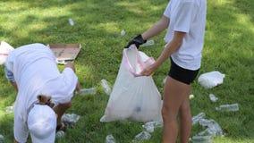 Wolontariuszi czyści śmieci w parku Ludzie podnosi w górę butelka klingerytu na trawie zbiory wideo