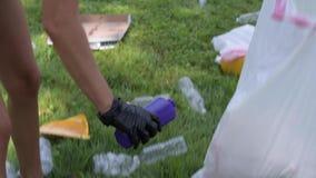 Wolontariuszi czyści śmieci w parku Ludzie podnosi w górę butelka klingerytu na trawie zdjęcie wideo