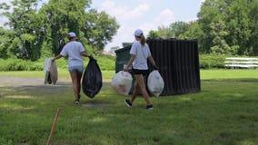 Wolontariuszi czyści śmieci w parku Ludzie z plastikowymi workami pełno śmieci, zanieczyszczenie środowiska zbiory