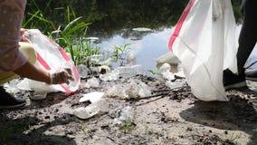 Wolontariuszi czyści śmieciarską pobliską rzekę Kobiety podnosi w górę butelka klingerytu w jeziorze kryzysu ekologiczny ?rodowis zdjęcie wideo