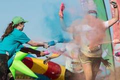 Wolontariuszi Oblewają biegaczów Z Barwionym Kukurydzanym krochmalem Przy koloru bieg Zdjęcia Royalty Free