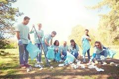 Wolontariuszi z torba na śmiecie czyści parkowego teren Fotografia Stock