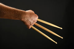 Wolverine hand with three drumsticks over black Royalty Free Stock Photos