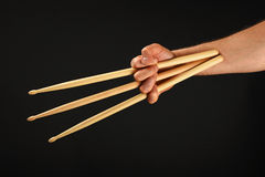 Wolverine hand with three drumsticks over black Royalty Free Stock Image
