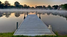 Dawn In The Great Lakes - Pure Michigan. This is Wolverine Lake, located in Southeast Michigan. Fog rolls over the water in the early morning new rising sun on Stock Photo