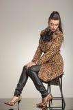 Woma μόδας που κάθεται και που στηρίζεται τα χέρια της στα γόνατά της Στοκ Εικόνες
