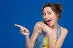 Woma alegre joven que señala los fingeres lejos Fotografía de archivo