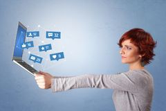 Woma holding laptop with social media notifications. Woman holding laptop with different types of social media symbols and icons stock images