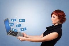 Woma holding laptop with social media notifications. Woman holding laptop with different types of social media symbols and iconsn royalty free stock photography