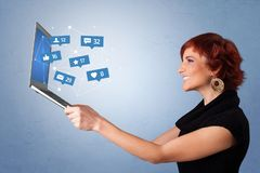Woma holding laptop with social media notifications. Woman holding laptop with different types of social media symbols and iconsn stock images