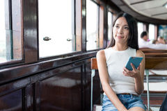 Woma holding smart phone inside ferry Royalty Free Stock Photos