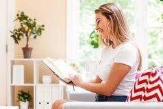 Woma joven que lee un libro Imagenes de archivo