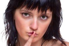 Woma mit ihrem Finger auf ihren Lippen Stockfotografie