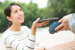 Woma paying on pos terminal by cellphone royalty free stock photo