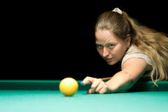 Woma playing billiards. On green table Royalty Free Stock Images