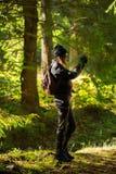 Woma que toma las fotos con el teléfono móvil en el bosque imagen de archivo