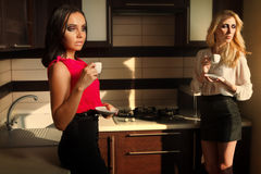 Womaen drinking coffee. Shot of sexy women drinking coffee in kitchen room Royalty Free Stock Images