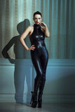Womam in catsuit posing at vintage wall Royalty Free Stock Image