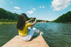 Womam que se sienta en un embarcadero del lago y que toma la imagen fotografía de archivo libre de regalías