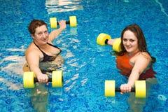 Womam zwei im Wasser mit Dumbbells Stockfotos