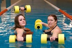 Womam zwei im Wasser mit Dumbbells Lizenzfreie Stockfotos