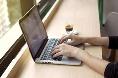 Woman's hands typing on notebook keyboard with coffee on desk. Woman's hands typing on notebook keyboard with coffee on wooden desk Stock Photography