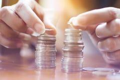 Woman's手指举行堆积在t的硬币银币两堆 免版税库存图片