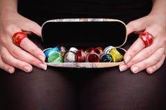 Woman's递拿着有许多各种各样的五颜六色的圆环的盘子 库存照片