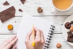 Woman's übergibt Schreiben in einem leeren Notizbuch, in der Tasse Tee und in den rohen Pralinen des strengen Vegetariers stockbilder