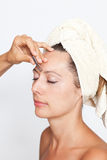 Woman's eyebrows being plucked. Eyebrows being plucked in a beauty spa royalty free stock photo