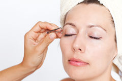 Woman's eyebrows being plucked Stock Image