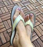 Woman's feet in white flip flop outdoor. Woman's feet in flip flop stock image