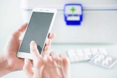 Woman's-Hände unter Verwendung des Smartphone für kaufende Drogen Lizenzfreie Stockbilder