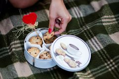 Woman's hand holding a cookie. Woman's hand holding one of cookies from the tin box standing on the checked plaid Royalty Free Stock Images