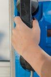 Woman's hand som rymmer en telefonmottagare Arkivbild