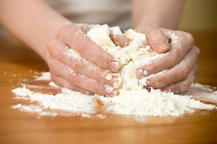 Woman�s hands knead dough on the table Royalty Free Stock Photos