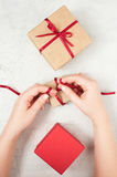 Woman's hands knotted red bow on the gift box Stock Photos