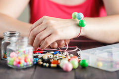 Woman's hands making bracelete with plastic beads Royalty Free Stock Images