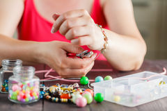 Woman's hands making bracelete with plastic beads Royalty Free Stock Image