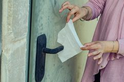 Woman's hygienic precautions when opening the door. A woman with germophobia prepares a napkin to cover the handle of the entrance door stock photography