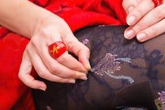 Woman's lägger benen på ryggen med härliga strumpor och händer med röda cirklar Royaltyfri Bild