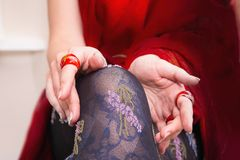 Woman's legs with beautiful stockings and hands with red rings Royalty Free Stock Photos