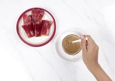 Woman'shand die een kop van koffie met djamboevruchten bewegen Royalty-vrije Stock Foto