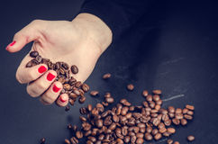 WomanÂ的手保留在黑暗的背景的咖啡豆 免版税库存照片