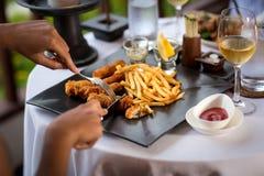 Χέρια Woman's που κόβουν το ψημένο στη σχάρα άσπρο πιάτο κρέατος Στοκ φωτογραφία με δικαίωμα ελεύθερης χρήσης