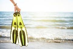 WomanÂs fena för snorkel och för simning för handuppehälle på en sandig strand konkurrensar som dyker pölsportar som simmar vatte Royaltyfria Bilder