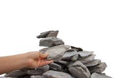 Womanâs Hand, die einen Felsen einem Steinhaufen hinzufügt lizenzfreie stockfotografie